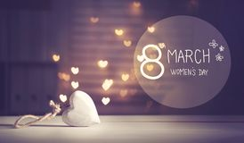 Happy Women`s Day message with a white heart. With heart shaped lights Stock Photography