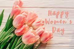 Happy women`s day text on pink tulips on white rustic wooden bac. Kground. greeting card concept. sensual tender womens image. spring flowers in soft morning Stock Photos