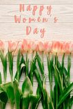 Happy women`s day text on pink tulips on white rustic wooden bac. Kground. greeting card concept. sensual tender womens image. spring flowers in soft morning Stock Photo
