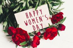 Happy women`s day text sign on craft card and beautiful red peon. Ies on white wooden rustic background, flat lay. modern greeting card. womens day Royalty Free Stock Photos