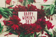 Happy women`s day text sign on craft card and beautiful red peon. Ies on wooden rustic background, flat lay. modern greeting card. womens day Stock Photos