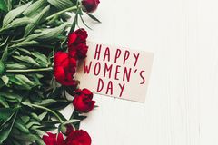 Happy women`s day text sign on craft card and beautiful red peon. Ies on white wooden rustic background, flat lay. modern greeting card. womens day Stock Photos
