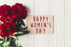 Happy women`s day text sign on craft card and beautiful red peon. Ies on white wooden rustic background, flat lay. modern greeting card. womens day Royalty Free Stock Photo