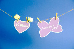 Happy Women`s Day. Women`s Day on paper , hanging on a rope with pink heart and flowers on blue background. Stock Photos
