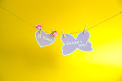 Happy Women`s Day. Women`s Day on paper , hanging on a rope with pink heart and flowers on golden background. Stock Photography