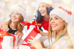 Happy women in santa hats with christmas gifts Royalty Free Stock Photos