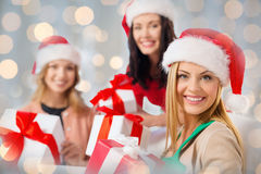 Happy women in santa hats with christmas gifts Stock Photos