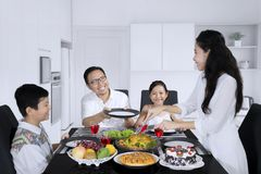 Happy woman is serving meals for her family. Happy women serving meals for her husband and children while having lunch together at home stock photo