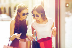 Happy women with shopping bags in city. Sale, consumerism and people concept - happy young women looking into shopping bags at shop window in city Royalty Free Stock Photos