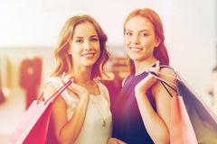 Happy women with shopping bags at clothing shop. Sale, consumerism and people concept - happy young women with shopping bags at clothing shop Royalty Free Stock Photography