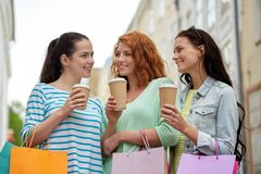 Happy women with shopping bags and coffee in city Stock Photo