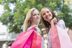 Happy women with shopping bags looking away Royalty Free Stock Photos