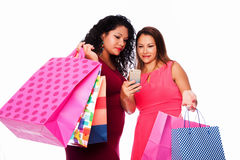 Happy women with shopping bags looking at phone Stock Photography