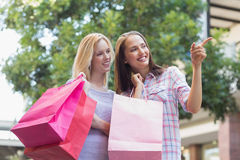 Happy women with shopping bags and pointing away Stock Photos