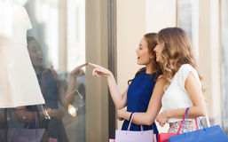 Happy women with shopping bags at shop window. Sale, consumerism and people concept - happy surprised young women with shopping bags pointing finger to shop Royalty Free Stock Photo