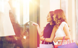 Happy women with shopping bags at shop window. Sale, consumerism and people concept - happy surprised young women with shopping bags pointing finger to shop Royalty Free Stock Image