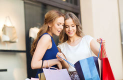Happy women with shopping bags at shop window Stock Images