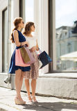 Happy women with shopping bags at shop window Royalty Free Stock Photos