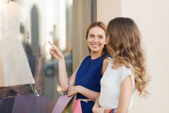 Happy women with shopping bags at shop window Stock Photos
