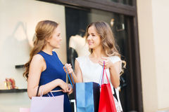Happy women with shopping bags at shop window Royalty Free Stock Image