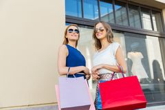 Happy women with shopping bags at storefront Royalty Free Stock Photo