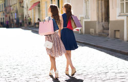 Happy women with shopping bags walking in city Stock Photos