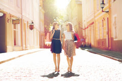 Happy women with shopping bags walking in city Royalty Free Stock Images