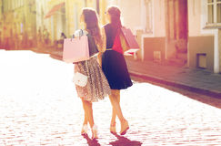 Happy women with shopping bags walking in city. Sale, consumerism and people concept - happy young women with shopping bags walking along city street Royalty Free Stock Photo