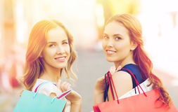 Happy women with shopping bags walking in city Stock Image