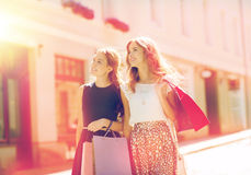 Happy women with shopping bags walking in city Stock Photo