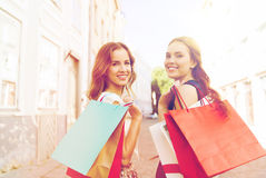 Happy women with shopping bags walking in city Royalty Free Stock Image