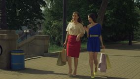 Happy women with shopping bags walking on the street stock video footage
