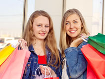 Happy women shopping and holding bags Royalty Free Stock Images