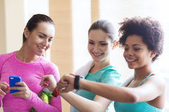 Happy women showing time on wrist watch in gym Royalty Free Stock Photo