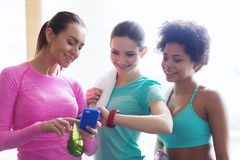 Happy women showing time on wrist watch in gym Royalty Free Stock Photos