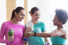 Happy women showing time on wrist watch in gym Stock Photo