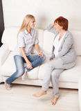 Happy women sitting at sofa Stock Photos