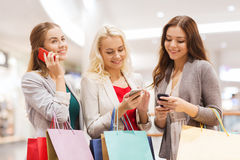 Happy women with smartphones and shopping bags Stock Images