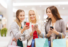 Happy women with smartphones and shopping bags Stock Image