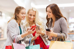 Happy women with smartphones and shopping bags. Sale, consumerism, technology and people concept - happy young women with smartphones and shopping bags in mall stock photos