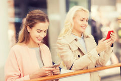 Happy women with smartphones and shopping bags Stock Photo