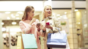 Happy women with smartphones and shopping bags. Sale, consumerism, technology and people concept - happy young women with smartphones and shopping bags talking stock footage