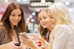 Happy women with smartphones and tablet pc in mall. Sale, consumerism, technology and people concept - happy young women with smartphones and tablet pc in mall royalty free stock photo