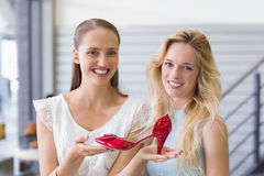 Happy women smiling at camera and showing a heel shoe Royalty Free Stock Images
