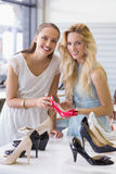 Happy women smiling at camera and showing a heel shoe Stock Images