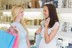 Happy women spraying perfume Royalty Free Stock Photo