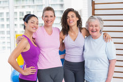 Happy women standing arms around in gym Royalty Free Stock Photo