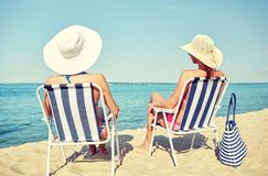 Happy women sunbathing in lounges on beach stock photo