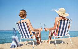 Happy women sunbathing in lounges on beach. Summer vacation, travel and people concept - happy women drinking beer and sunbathing in lounges on beach Stock Photos