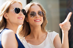 Happy women in sunglasses pointing finger outdoors Stock Photos